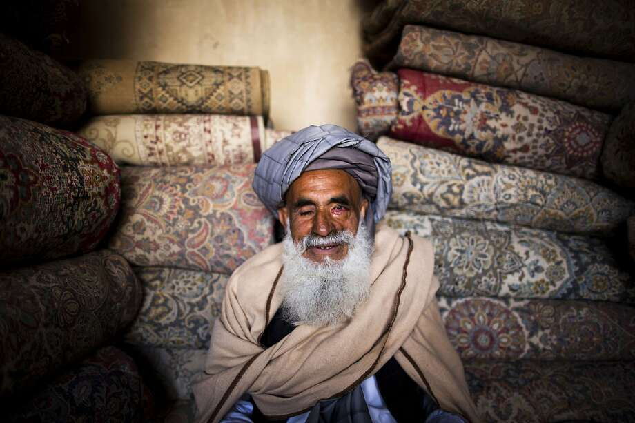 TOPSHOTS Afghan carpet seller Ahmad Shah, who sells Iranian machine-made carpets, poses for a photograph in his carpet shop in the northwestern city of Herat on April 2, 2014. Carpets are Afghanistan's best-known export, woven mostly by women and children in the north of the country, a trade which once employed, directly or indirectly, six million people, or a fifth of the country's population, but that figure has dropped sharply. AFP PHOTO/BEHROUZ MEHRIBEHROUZ MEHRI/AFP/Getty Images Photo: Behrouz Mehri, AFP/Getty Images
