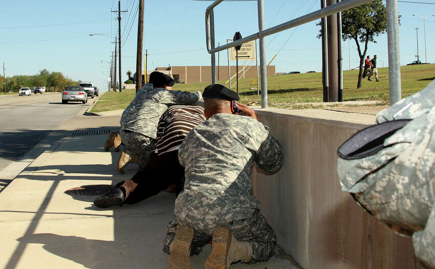 In this image released by the U.S. Army, bystanders crouch for cover as shots rang out from Fort Hood's Soldier Readiness Processing Center Thursday, Nov. 5, 2009, as law enforcement officers run toward the sound of the gunfire at Fort Hood, Texas. Army psychiatrist Maj. Nidal Malik Hasan is accused of firing more than 100 rounds Thursday, killing 13 and wounding others, in the soldier processing center at Fort Hood. (AP Photo/U.S. Army, Jeramie Sivley)