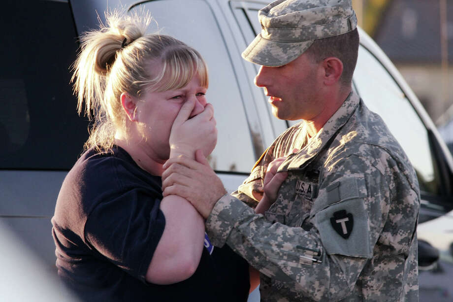 FILE - Sgt. Anthony Sills, right, comforts his wife as they wait outside the Fort Hood Army Base near Killeen, Texas on Thursday, Nov. 5, 2009. The Sills' 3-year old son is still in daycare on the base, which is in lock-down following a mass shooting earlier in the day. (AP Photo/Jack Plunkett) Photo: Jack Plunkett, Associated Press / AP2009