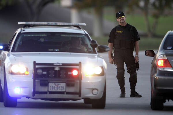 Authorities guard the the closed entrance of Fort Hood, Texas, after a shooting on the base, Thursday, Nov. 5, 2009. (AP Photo/LM Otero)