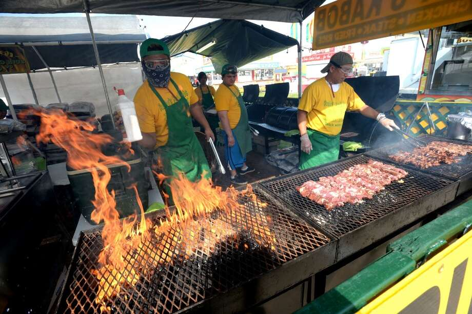 Ray Ferrer, left and Pat Sebastian cook up a mess of kabobs at Rudy's at the South Texas State Fair. Photo taken Friday, March 28, 2014 Guiseppe Barranco/@spotnewsshooter