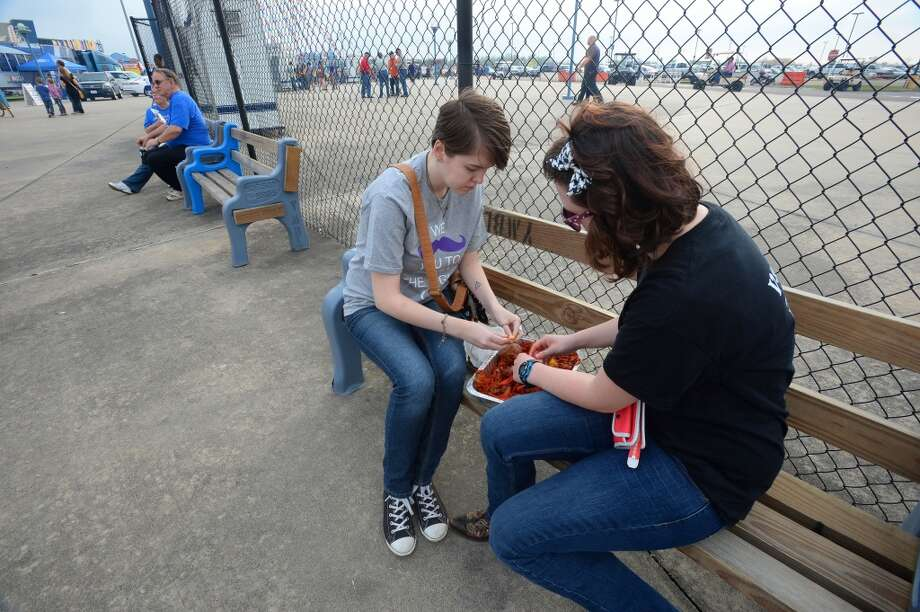 Regan Day, left, and Blair Bonnette eat crawfish on a bench at the South Texas State Fair. Photo taken Friday, March 28, 2014 Guiseppe Barranco/@spotnewsshooter