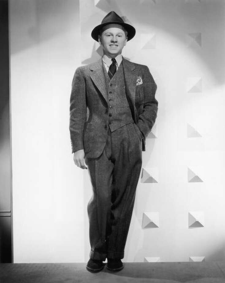 American actor Mickey Rooney wears a three-piece tweed suit and a hat and stands with his hand in his pants pocket, in a full-length promotional portrait for director George B Seitz's film, 'A Family Affair'. Actor Mickey Rooney died Sunday, April 6, 2014, at age 93. Photo: Hulton Archive, Getty Images / Moviepix