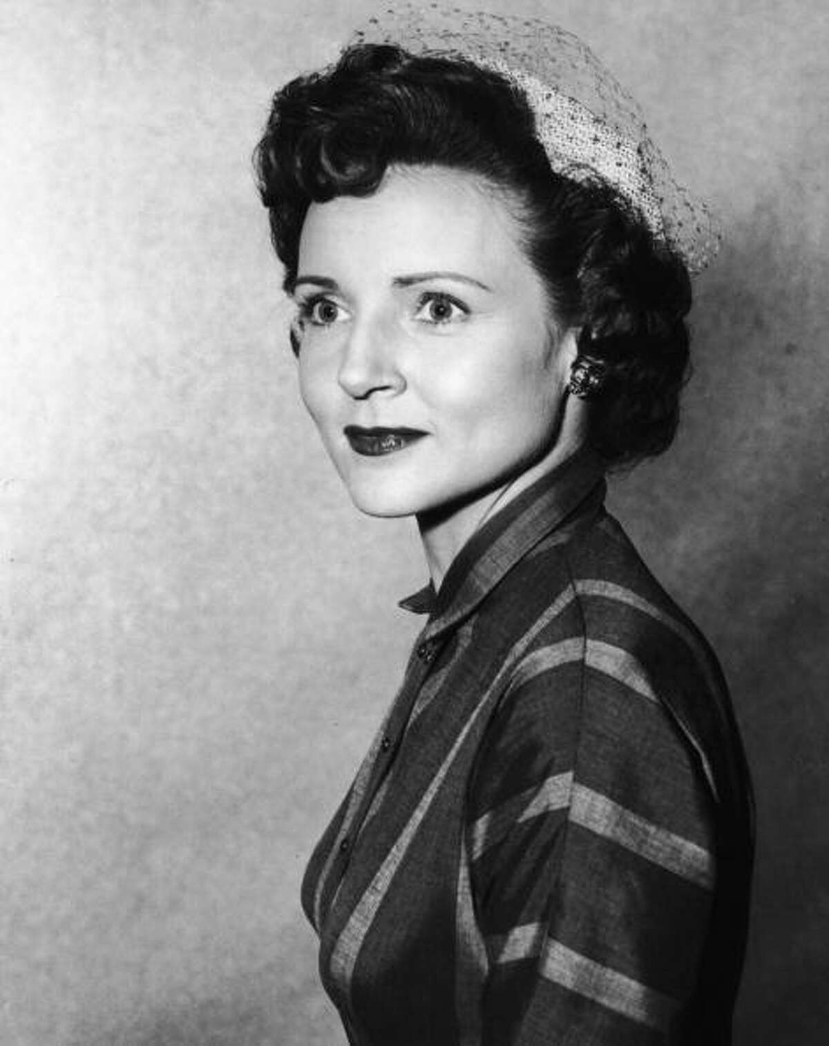 A headshot portrait of American actor Betty White wearing a veiled hat, circa 1955.