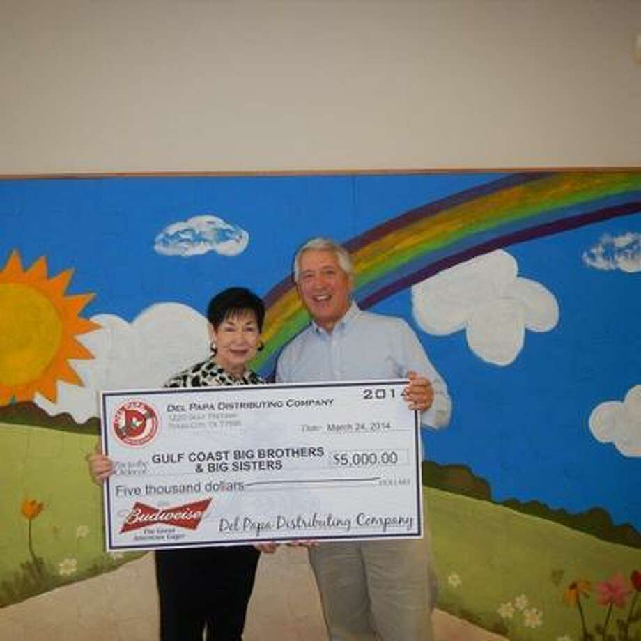 Peter Williamson, vice president of business and community relations for Del Papa Distributing Company, presents a check to Cindy Shultz, executive director, Gulf Coast Big Brothers & Big Sisters Inc.