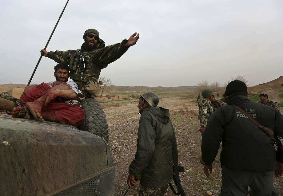 Afghan soldiers carry a wounded Taliban fighter after a gunbattle in a village in Herat province. Photo: Omar Sobhani, Reuters