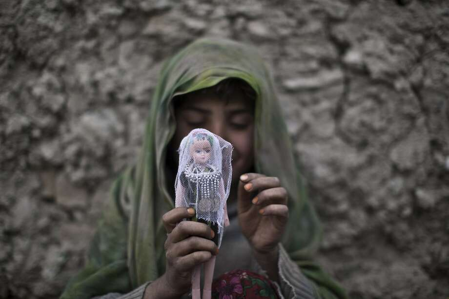 An Afghan girl dresses her doll while playing in an alley in Kabul. Photo: Muhammed Muheisen, Associated Press