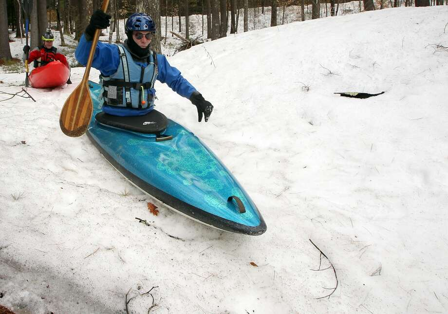 Watch out for the trees, guys! Jack Fuller (front) and Jeff Fluet slide down a snow embankment into the Contoocook River in 