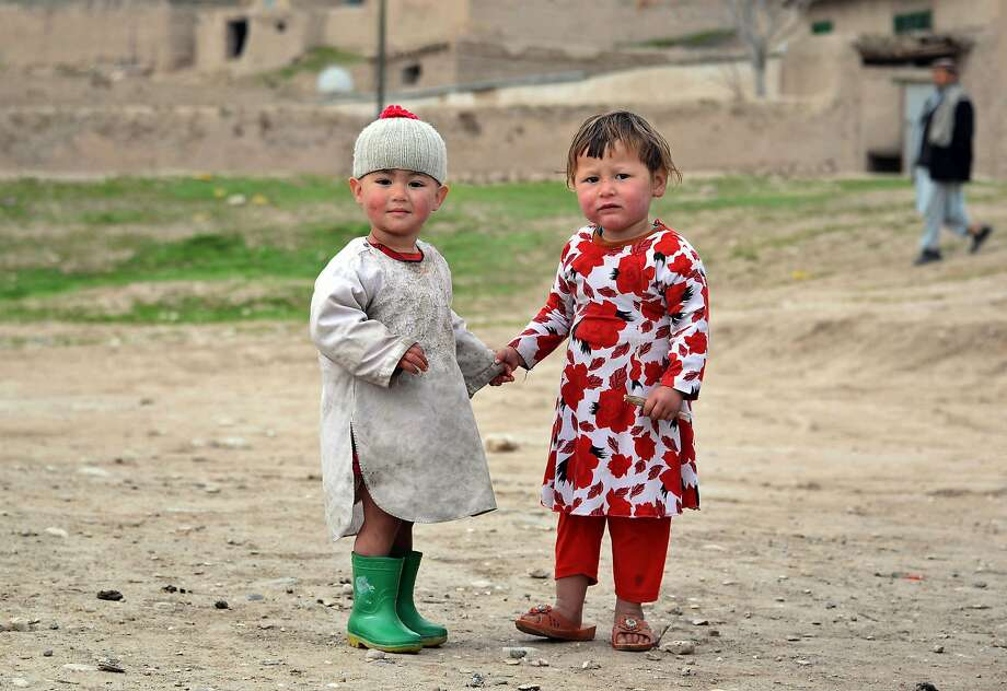 Expecting rain, are we, Green Galoshes? Afghan kids hold hands in the Kishindih district of 
