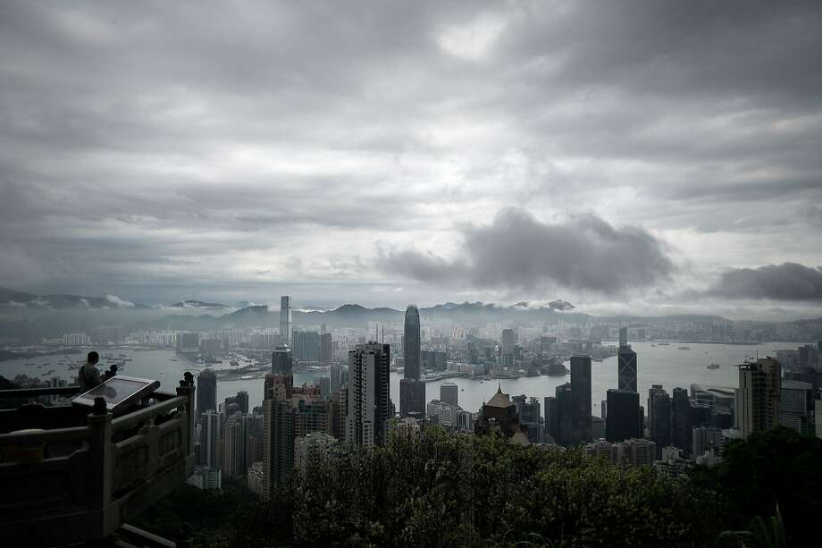 Weather watch: A man looks out over the downtown skyline as a storm approaches Hong Kong. Photo: Philippe Lopez, AFP/Getty Images