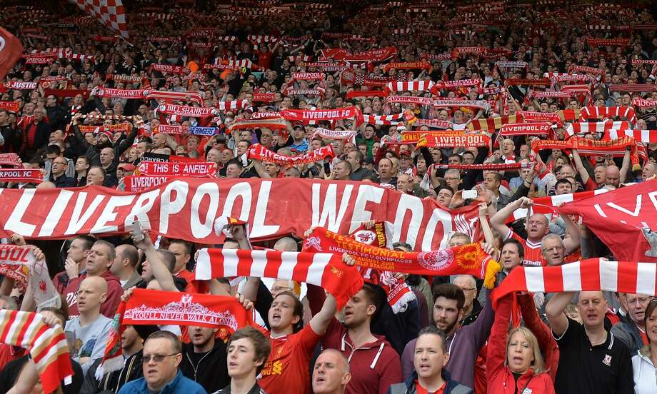 Liverpool fans, holding up scarves in support during a home match last week, have something to cheer once again. The Reds lead the English Premier League with six matches to go. Photo: Paul Ellis, AFP/Getty Images