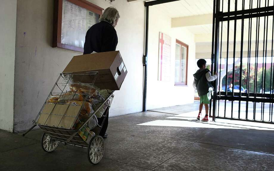 A woman pulls a cart filled with food she received from a food bank in California. Although many programs are available to assist the working poor, 40 to 50 percent of people eligible for food assistance — both locally and nationally — do not participate in them. Photo: Justin Sullivan / Getty Images / oped hunger