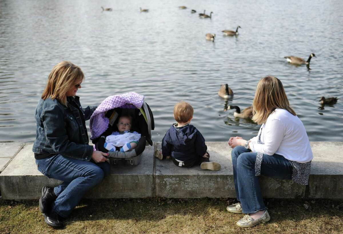 From left, grandmother Susan Nute, Logan Collins, 5 months, Bentley Collins, 2, and mother Lauren Collins, of Newtown, feed geese at Hawley Pond in Newtown, Conn. Thursday, April 3, 2014.