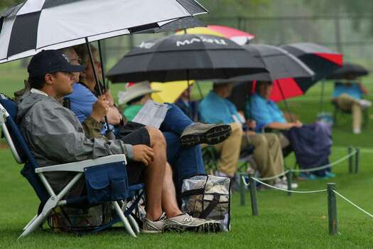 Nishant Naik of Houston watches the Shell Houston Open first round from the first hole sidelines under the protection of his umbrella during a rainy day of golf, Thursday, April 3, 2014, in Humble. Photo: Marie D. De Jesus, Houston Chronicle / © 2014 Houston Chronicle