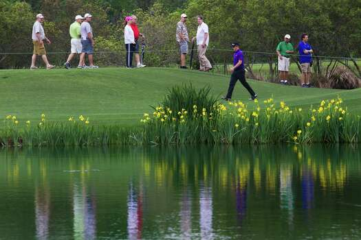Golfers and fans walk by the 18th hole water trap during the Shell Houston Open first round Thursday, April 3, 2014, in Humble. Photo: Marie D. De Jesus, Houston Chronicle / © 2014 Houston Chronicle