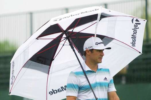 Trevor Immelman protects himself from the rain at the first hole green during the Shell Houston Open, Thursday, April 3, 2014, in Humble. Photo: Marie D. De Jesus, Houston Chronicle / © 2014 Houston Chronicle