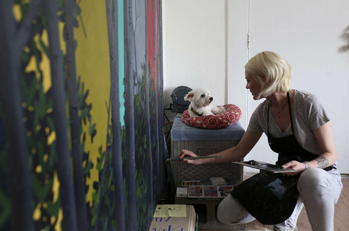 Frantz paints in her studio with her dog, Rosco. She soon will leave UTSA for a teaching position in California.