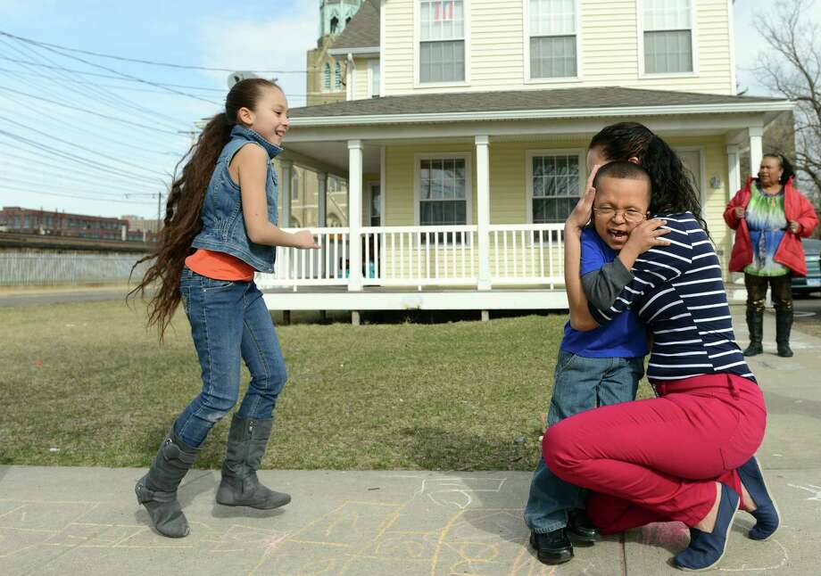 Six-year-old Michael Rodriguez hugs his mother Ana while playing hopscotch with his siter Denisse, 9, Thursday, April 3, 2014, at their home in Bridgeport, Conn. Michael has a rare condition called Cardio-Facio-Cutaneous (CFC) syndrome, marked by congenital heart defects, scoliosis, eye problems, learning disabilities and other problems. The family is trying to raise money to attend a conference in Florida this summer where they can spend time with other children with Michael's condition and meet the doctor who discovered CFC sydrome. Photo: Autumn Driscoll / Connecticut Post