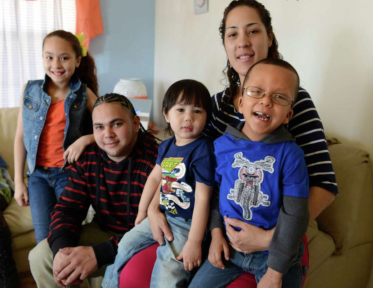 The Rodriguez family, from left, Denisse, 9, Victor Alexis, Alexis, 2, Ana and Michael, 6, sit together Thursday, April 3, 2014, at their home in Bridgeport, Conn. Michael Rodriguez, a student at Waltersville School, has a rare condition called Cardio-Facio-Cutaneous (CFC) syndrome, marked by congenital heart defects, scoliosis, eye problems, learning disabilities and other problems. The family is trying to raise money to attend a conference in Florida this summer where they can spend time with other children with Michael's condition and meet the doctor who discovered CFC sydrome.