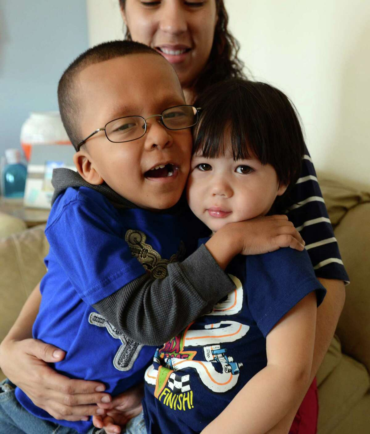 Six-year-old Michael Rodriguez gives his younger brother Alexis, 2, a hug, Thursday, April 3, 2014, at their home in Bridgeport, Conn. Michael has a rare condition called Cardio-Facio-Cutaneous (CFC) syndrome, marked by congenital heart defects, scoliosis, eye problems, learning disabilities and other problems. The family is trying to raise money to attend a conference in Florida this summer where they can spend time with other children with Michael's condition and meet the doctor who discovered CFC sydrome.