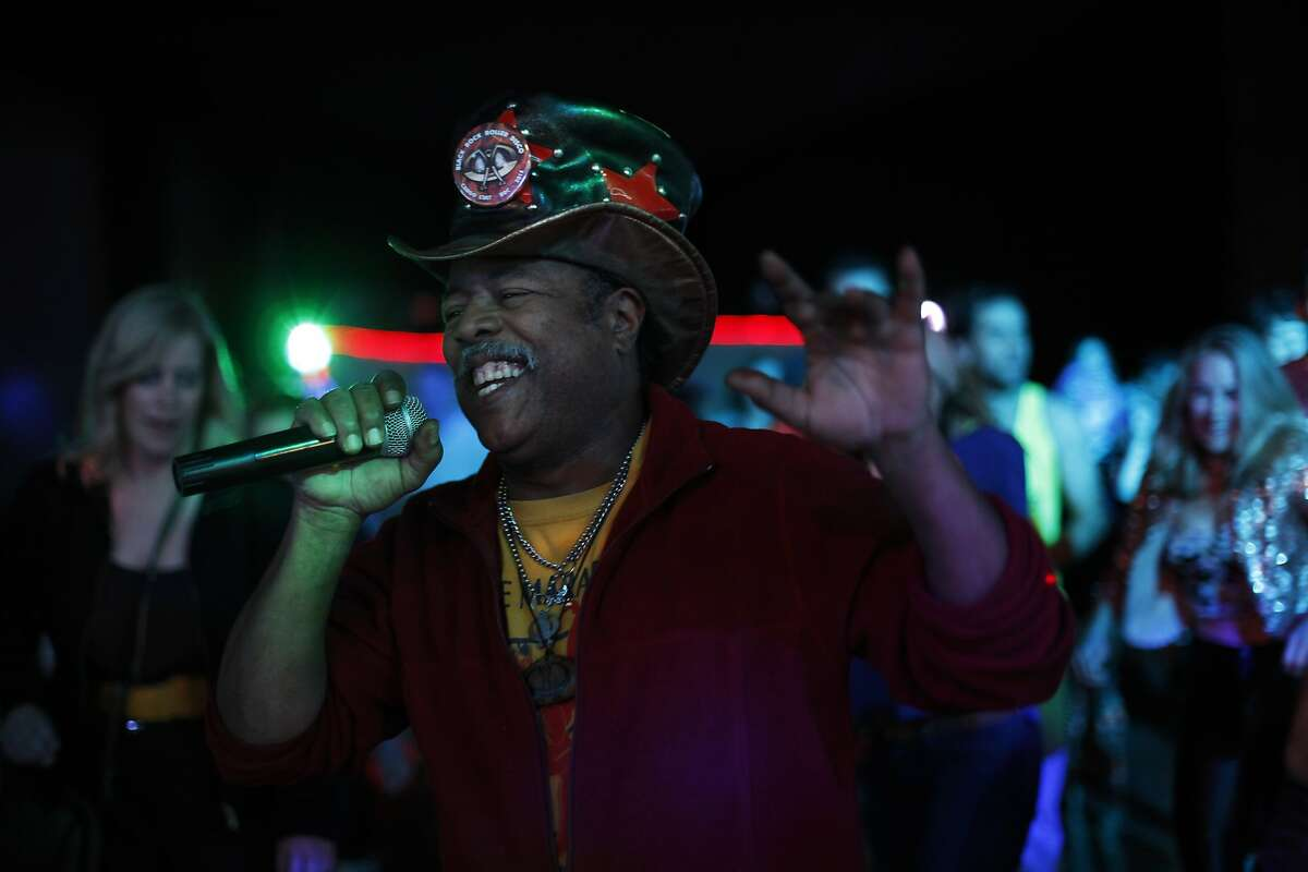 David Miles Jr. leads the crowd in a line dance. The longtime roller-skating enthusiast has outfitted Sacred Heart with a disco ball, flashing strobe lights and a first-class sound system.
