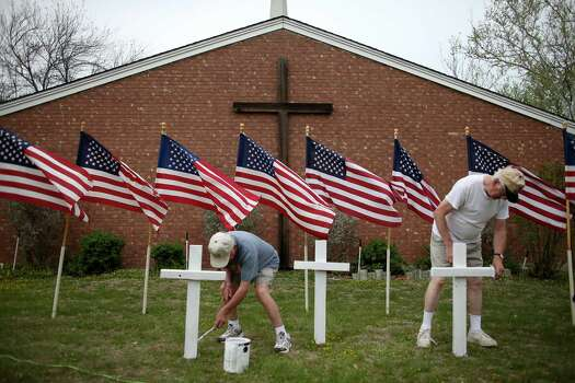 FORT HOOD, TX - APRIL 03:  Bob Butler (L) and Bob Gordon paint crosses they placed in front of 16 American flags as they build a memorial in front of Central Christian Disciples of Christ church for the victims of yesterdays shooting at Fort Hood on April 3, 2014 in Killeen, Texas. Iraq war veteran, Ivan Lopez, is reported to be the shooter that claimed three lives and wounded 16 more before taking his own life at Fort Hood. Photo: Joe Raedle, Getty Images / 2014 Getty Images