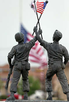 Soldier statues holding flags at a Korean War memorial at the Killeen Civic and Conference Center are contrasted against  half mast flags nearby on April 3, 2014. Photo: TOM REEL