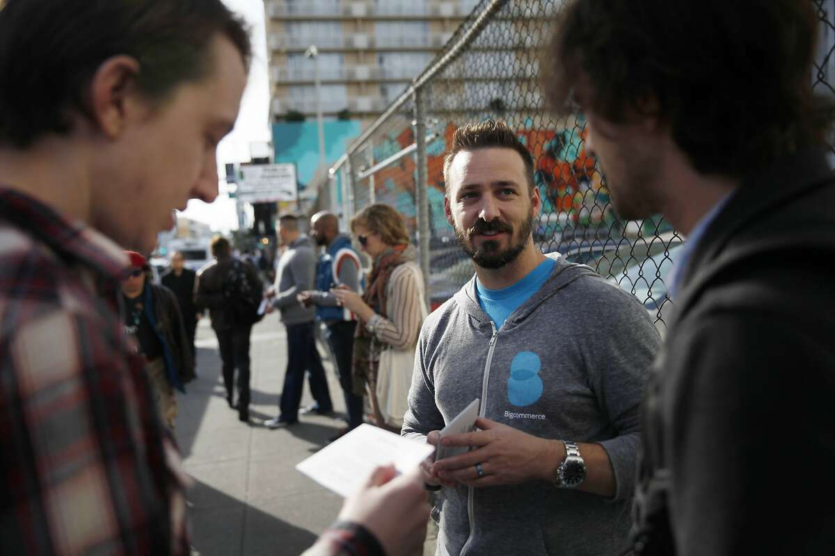 Steve Donnelly (center), Bigcommerce human resources and recruiting, talks with Josh Southern (left) of San Francisco and a Google engineer (right) as he hands out invite cards for a happy hour at Bigcommerce's engineering office to people at a shuttle stop along 8th Street at Market Street on Thursday, April 3, 2014, in San Francisco, Calif.