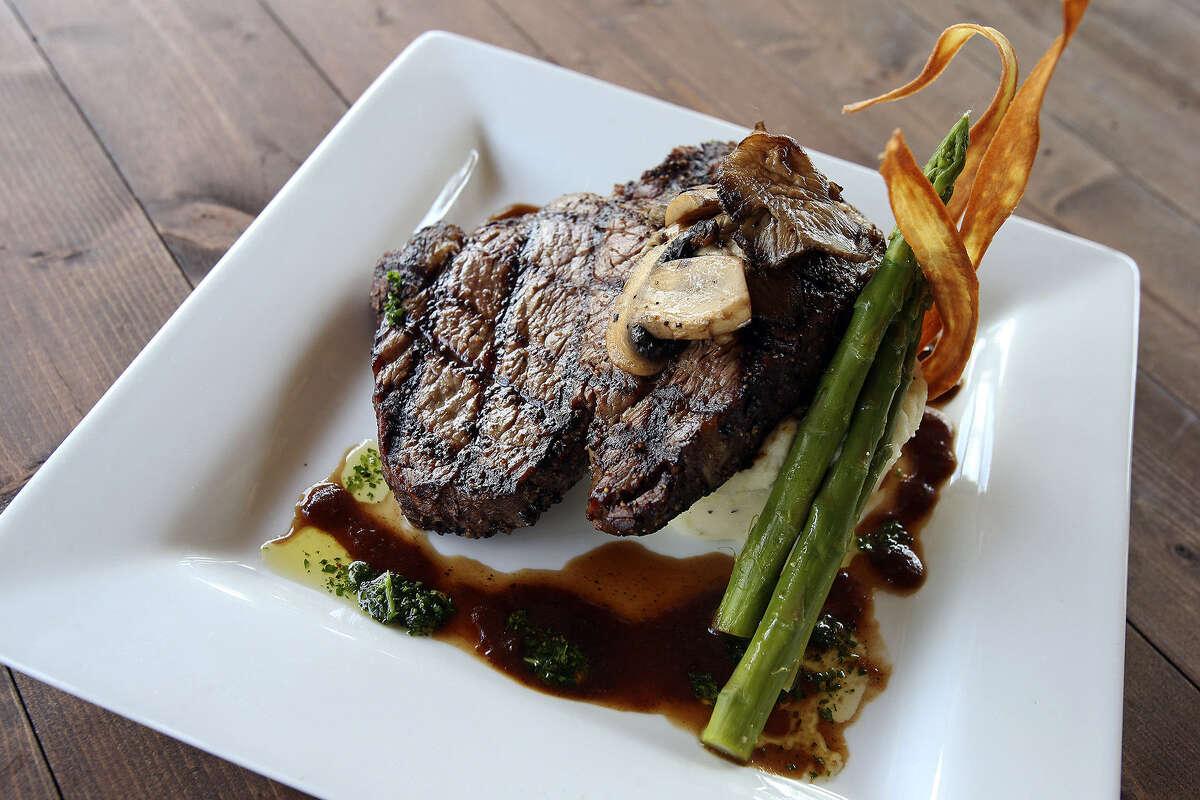 A perfectly prepared rib-eye steak is served with wild mushrooms, roasted garlic mashed potatoes and seasonal vegetables.