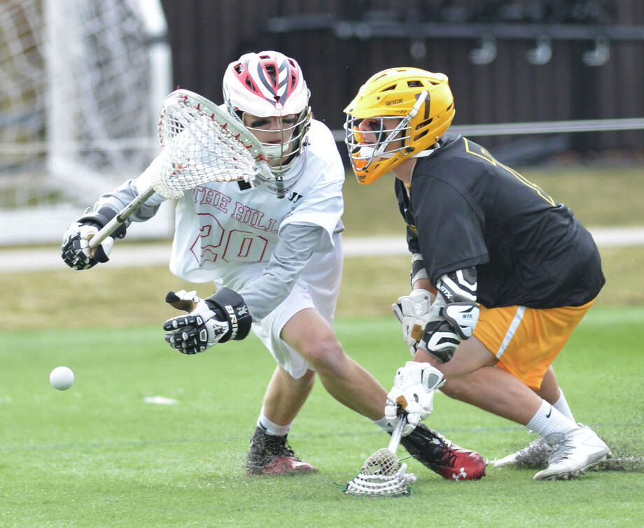 At left, Hill Academy goalie Hayden Walsh (#20) loses the ball while being pressured by Brunswick's Alex Buckanavage (#7), right, during the high school lacrosse match between Brunswick School and Hill Academy of Ontario, Canada, at Brunswick in Greenwich, Conn., Thursday, April 3, 2014. Photo: Bob Luckey / Greenwich Time