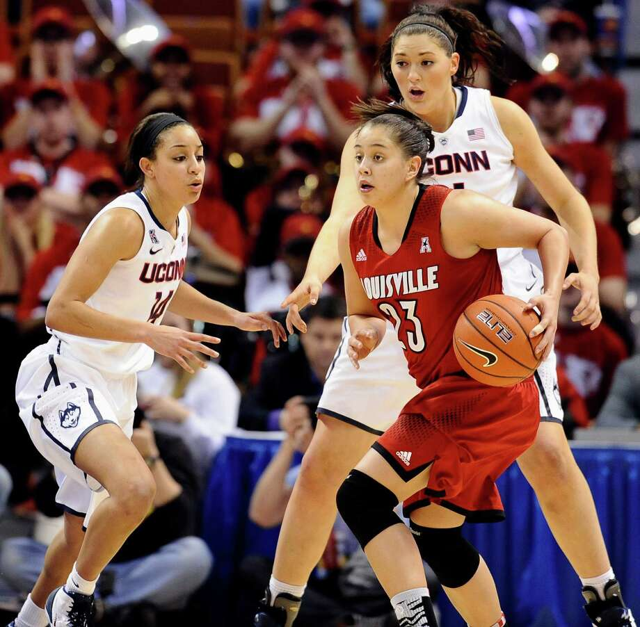Louisville's Shoni Schimmel, front center, looks to pass as Connecticut's Bria Hartley, left, and Stefanie Dolson, right, defend during the first half of an NCAA college basketball game in the finals of the American Athletic Conference women's basketball tournament, Monday, March 10, 2014, in Uncasville, Conn. Connecticut won 72-52. Photo: Jessica Hill, AP / Associated Press