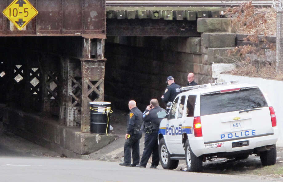 MTA police investigated a suspicious black barrel found near a railroad overpass in Bridgeport, Conn. on April 3, 2014. The barrel was found to be property of the Metro-North Railroad and was filled with painting coveralls and respirator masks. Photo: Wes Duplantier / Connecticut Post