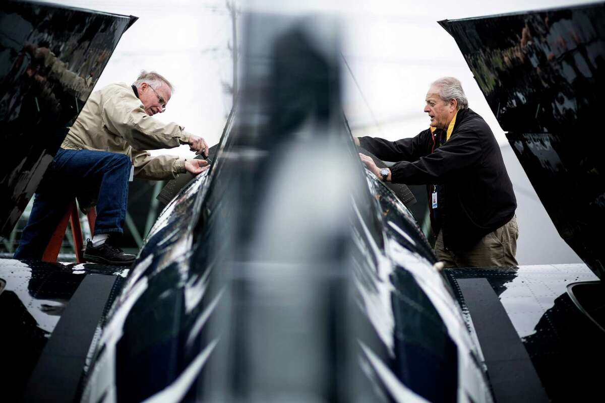 Nick Peak, left, and Gary Lollis, right, work to move a WWII-era FM-2 Wildcat fighter plane into its new permanent home Thursday, April 3, 2014, at the Museum of Flight in Seattle.