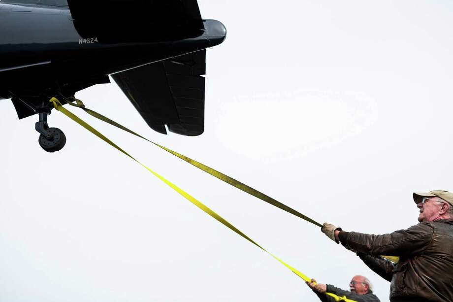 Following nearly two decades of restoration, Barry Horner, right, joins volunteers and other Museum of Flight employees to help move a WWII-era FM-2 Wildcat fighter plane into its new permanent home Thursday, April 3, 2014, at the Museum of Flight in Seattle. Photo: JORDAN STEAD, SEATTLEPI.COM / SEATTLEPI.COM