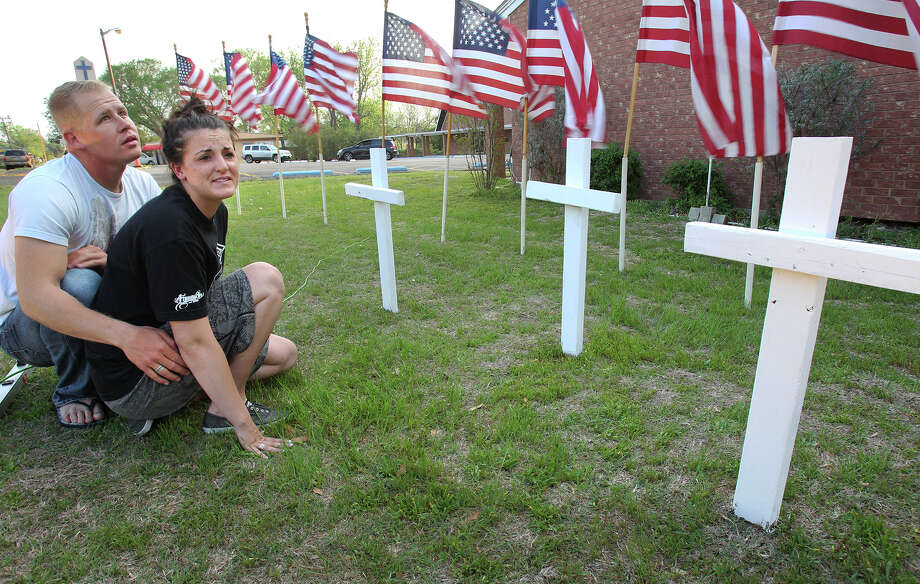 Tearful soldiers, U.S. Army enlisted Brandon Dunn, Baton Rouge, Louisiana and Elissa Landry, Phoeniz Arizona stop to say a prayer under three crosses placed in front of the Central Christian church in Killeen on April 3, 2014.  Dunn is friends with one of the the soldiers wounded in Wednesday's shooting at Ft. Hood. Photo: TOM REEL