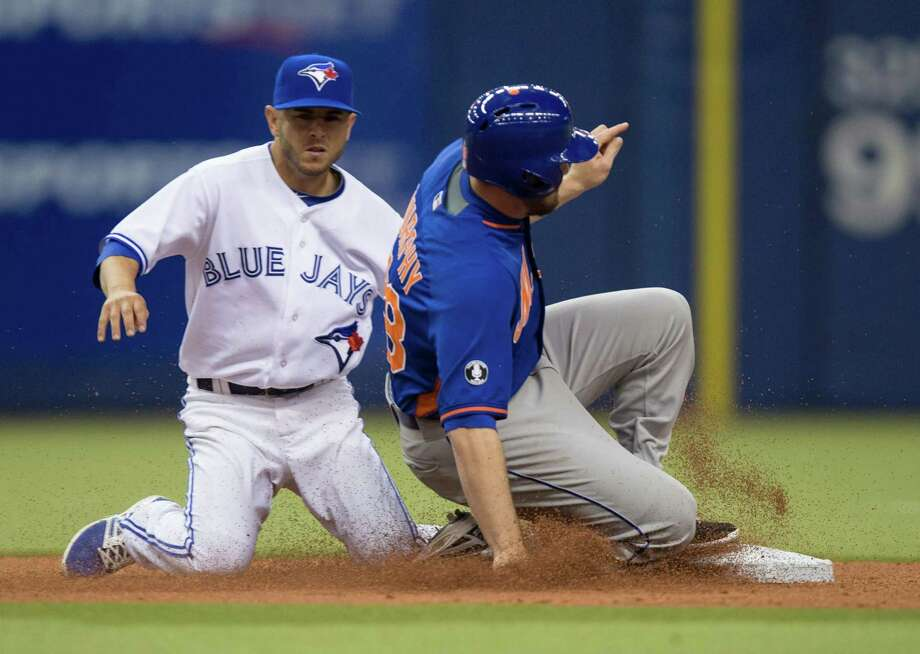 New York Mets' Daniel Murphy is tagged out by Toronto Blue Jays shortstop Jonathan Diaz while attempting to steal second base during sixth inning of an exhibition baseball game Saturday, March 29, 2014, in Montreal. (AP Photo/The Canadian Press, Paul Chiasson) ORG XMIT: PCH120 Photo: Paul Chiasson / CP