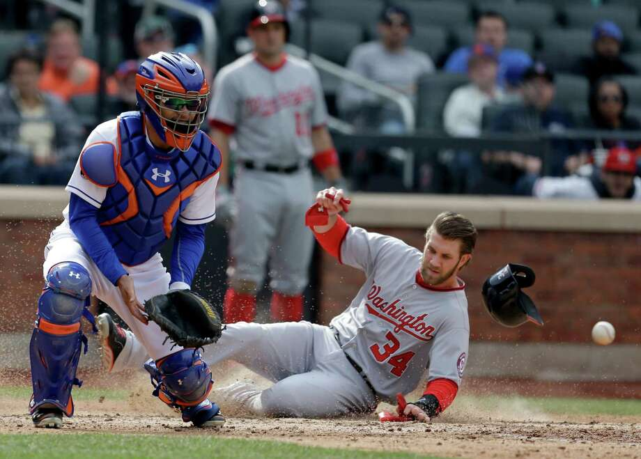 While New York Mets catcher Travis d'Arnaud, left, waits for the ball, Washington Nationals' Bryce Harper slides safely home during the seventh inning of the baseball game at Citi Field, Thursday, April 3, 2014 in New York. (AP Photo/Seth Wenig) ORG XMIT: NYM115 Photo: Seth Wenig / AP