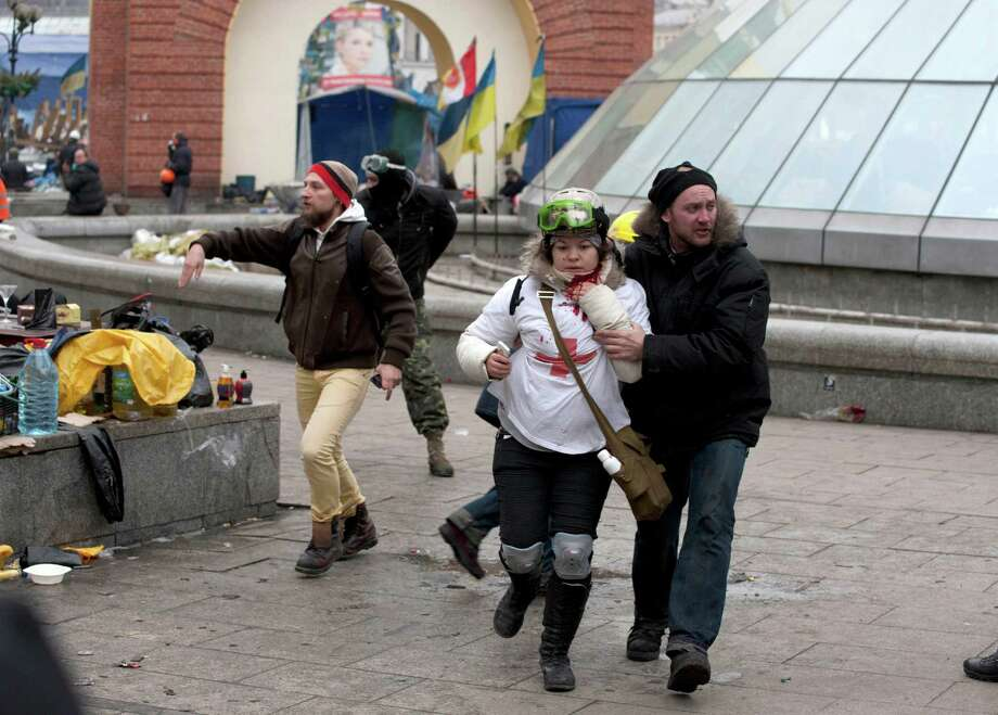 """FILE - In this file photo taken on Thursday, Feb.  20, 2014, Olesya Zhukovska, left, is helped after being shot in her neck by a sniper bullet, in Independence Square, the epicenter of the country's current unrest, Kiev, Ukraine.  """"I am dying"""", Olesya Zhukovska, a 21-year-old volunteer medic, wrote on Twitter, minutes after she got shot in the neck by a sniper's bullet as deadly clashes broke out in the center of the Ukrainian capital between protesters and police. The tweet, accompanied by a photo of her clutching her bleeding neck and being led away under fire, went viral, as social media users around the world presumed she had died and shared their grief and anger. Authorities in Ukraine said on Thursday that they have detained several members of an elite riot police unit on suspicion of shooting protesters during bloody anti-government clashes in February that left more than 100 dead. (AP Photo/Alexander Sherbakov, File) ORG XMIT: MOSB104 Photo: Alexander Sherbakov / AP"""