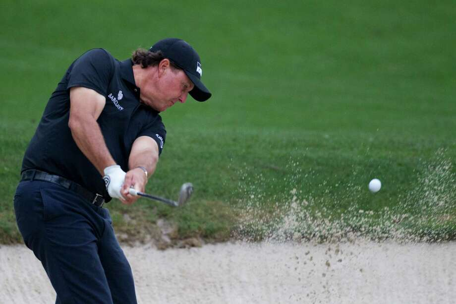 Phil Mickelson shows how it's done from a bunker on No. 13 during his bogey-free, 4-under 68 opening round Thursday. Photo: Marie D. De Jesus, Staff / © 2014 Houston Chronicle