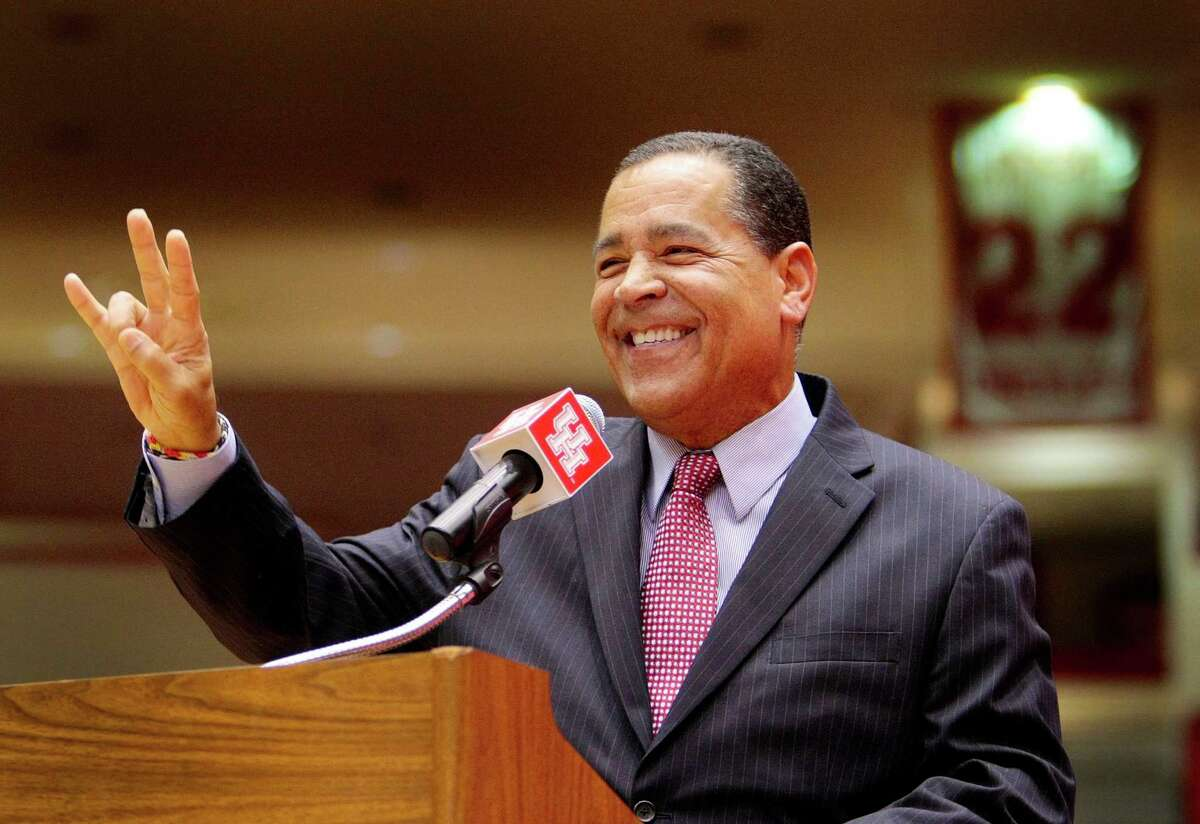 """Kelvin Sampson throws up UH's """"Cougar Paw"""" sign after being introduced as the school's new men's basketball coach Thursday."""