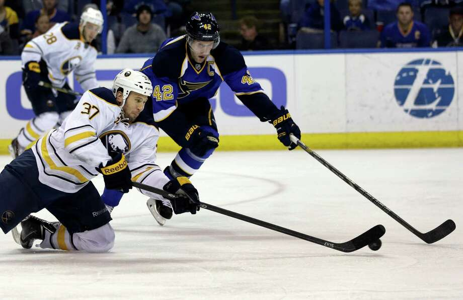 Buffalo Sabres' Matt Ellis, front left, and St. Louis Blues' David Backes chase after a loose puck during the second period of an NHL hockey game on Thursday, April 3, 2014, in St. Louis. (AP Photo/Jeff Roberson)  ORG XMIT: MOJR109 Photo: Jeff Roberson / AP