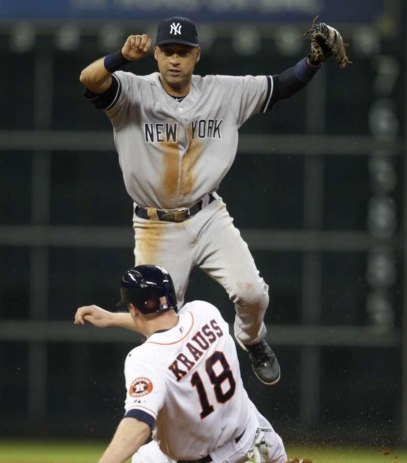 Yankees shortstop Derek Jeter jumps over Astros left fielder Marc Krauss after Alex Presley grounded out. Photo: Karen Warren, Houston Chronicle