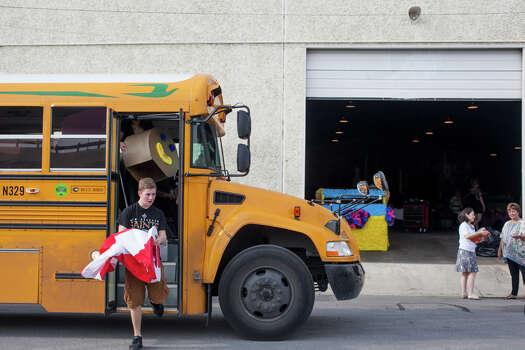 Marshall High School junior Joel Dugas, 16, unloads costumes and props from their school bus during Thursday's dress rehearsal. Photo: Julysa Sosa / Julysa Sosa For the San Antonio Express-News