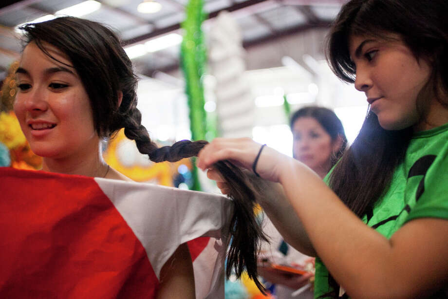 Marshall High School junior Serena Casanova (from left), 17, has her hair braided by junior Jessica Cantu, 17, before practicing aboard their float during Thursday's dress rehearsal. Photo: Julysa Sosa / Julysa Sosa For the San Antonio Express-News