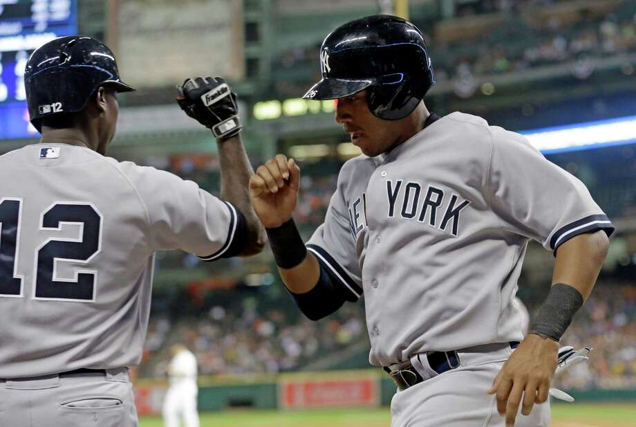 New York Yankees' Yangervis Solarte, right, knock arms with teammate Alfonso Soriano (12) after scoring from third base on a Carlos Beltran bases-loaded sacrifice fly against the Houston Astros in the third inning of a baseball game on Thursday, April 3, 2014, in Houston. (AP Photo/Pat Sullivan) ORG XMIT: HTA107 Photo: Pat Sullivan / AP