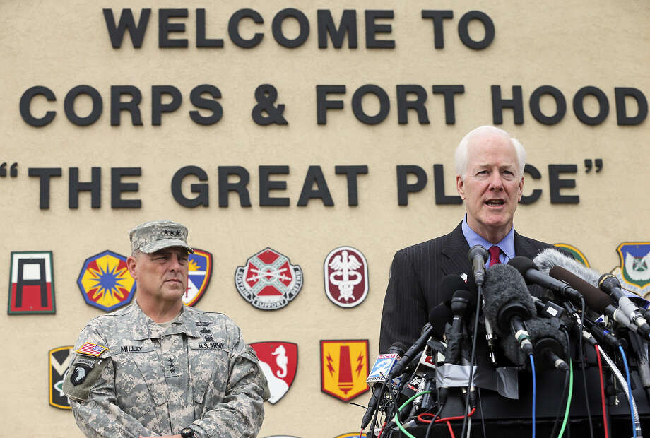 With Lt. Gen. Mark Milley looking on, Sen. John Cornyn, R-Texas, answers questions from members of the news media at Fort Hood. Cornyn traveled to the post on Thursday. Photo: Tom Reel / San Antonio Express-News