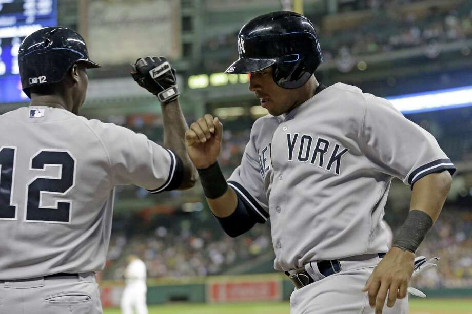 New York's Yangervis Solarte (right) greets Alfonso Soriano after scoring on a sacrifice fly in Houston. Photo: Pat Sullivan / Associated Press / AP