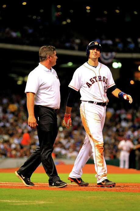 Jason Castro, right, is escorted to first base by trainer Nate Lucero after getting hit a second time Thursday by Yankees pitcher Ivan Nova. Castro left the game shortly thereafter. Photo: Karen Warren, Staff / © 2014 Houston Chronicle