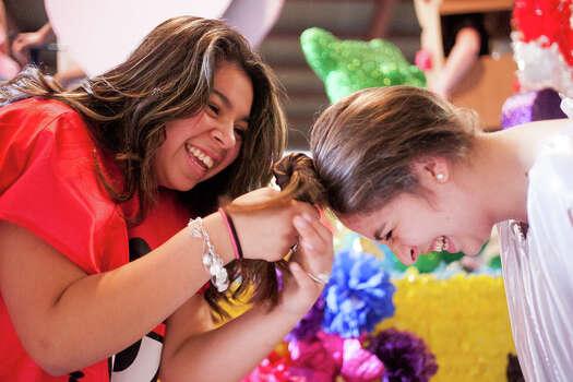 Marshall High School freshman Jamie Garibay (from left), 14, fixes sophomore Amanda Pittman's hair during Thursday's dress rehearsal. Photo: Julysa Sosa, For The San Antonio Express-News / Julysa Sosa For the San Antonio Express-News