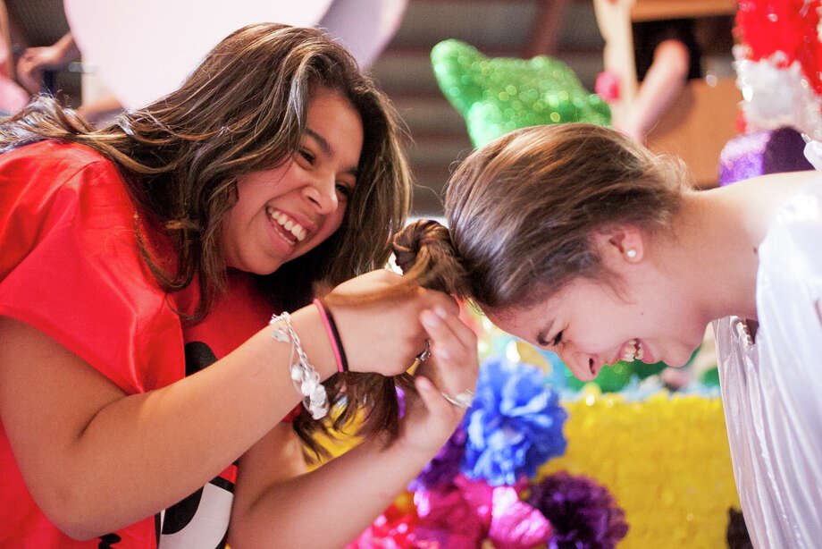 Marshall High School freshman Jamie Garibay (from left), 14, fixes sophomore Amanda Pittman's hair during Thursday's dress rehearsal. Photo: Julysa Sosa, For The San Antonio Express-News / Julysa Sosa For the San Antonio Express-News